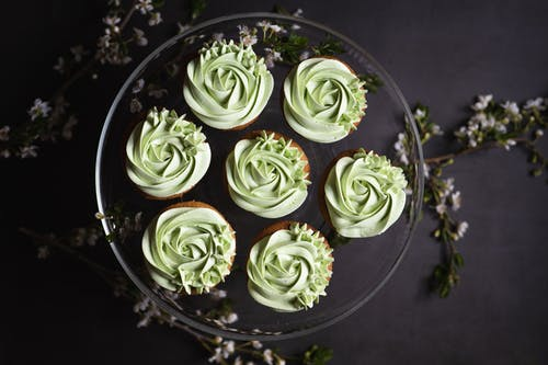 Green and White Flower Petals on Black Round Plate
