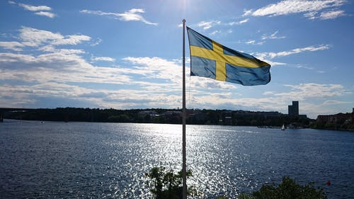 Kostnadsfri bild av blå himmel, svensk flagga, vid havet