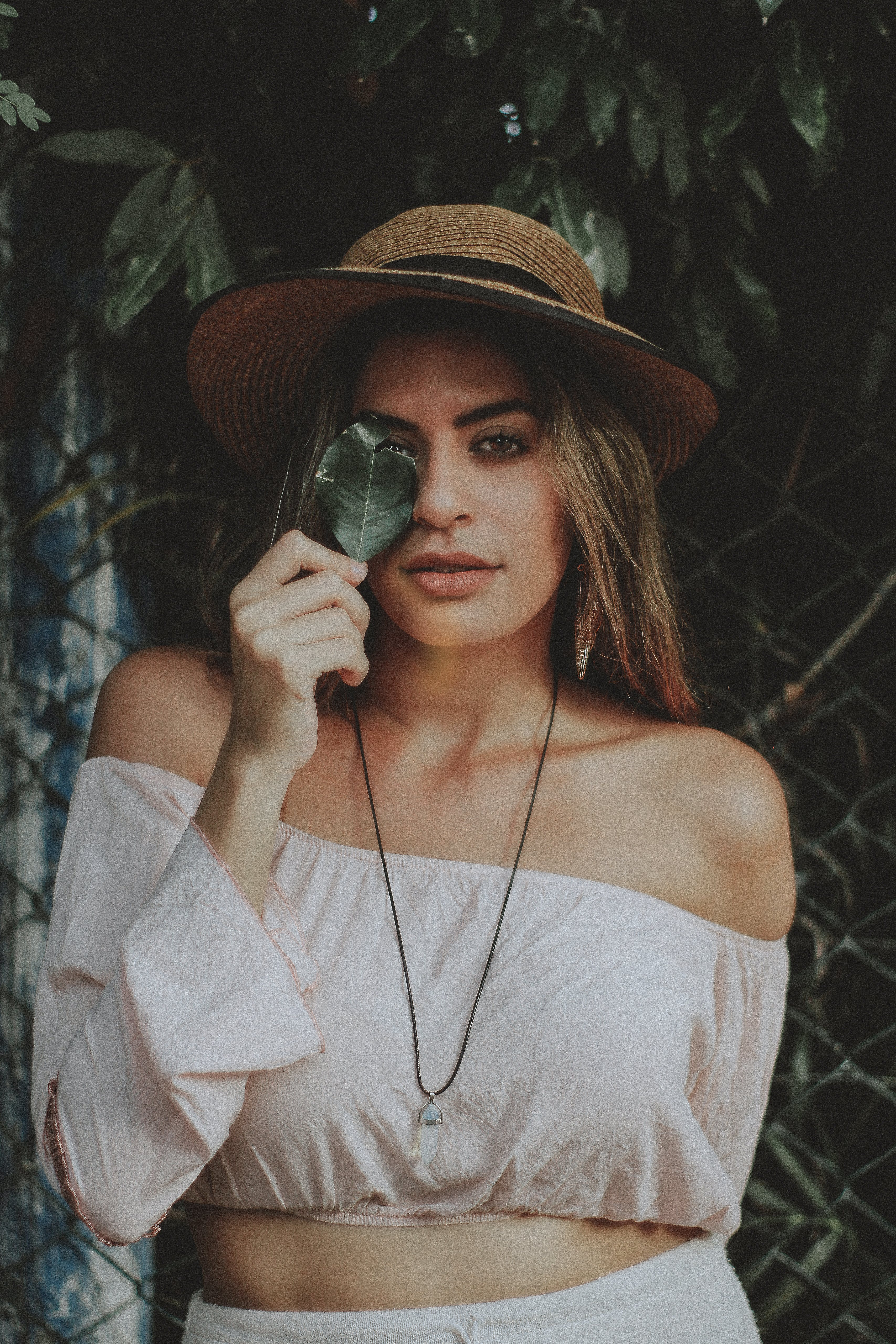 Woman in Crop Top Holding Leaf Covering Right Eye