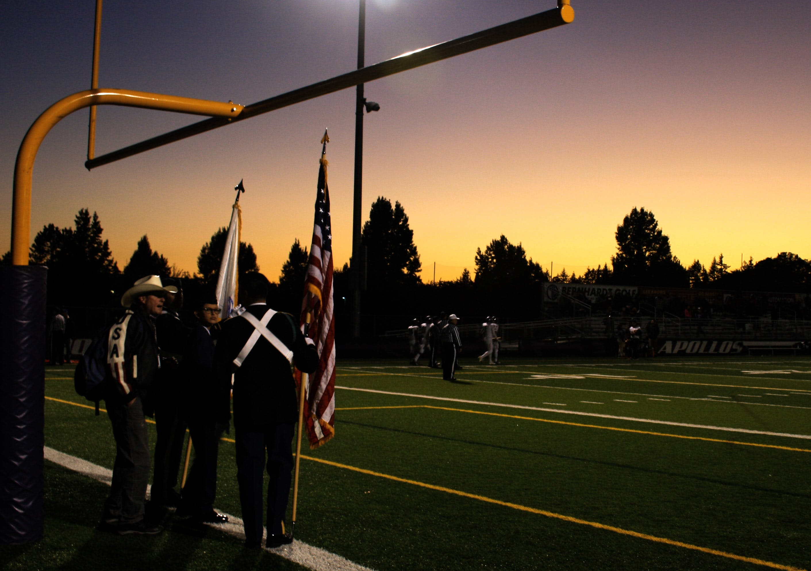 Four People Standing Under on Football Goal during Sunrise