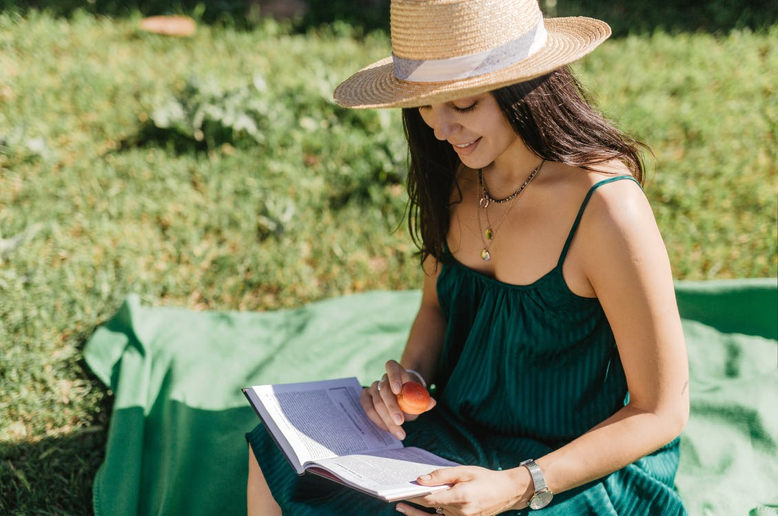 From above of happy young female with long dark hair in stylish dress and straw hat sitting on blanket on grassy lawn and reading interesting book during picnic in park