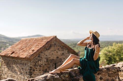 Woman in Teal Sleeveless Dress Sitting on Brown Rock