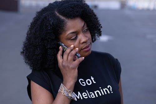 Close-Up Shot of an Afro-Haired Woman in Black Shirt Having a Phone Call