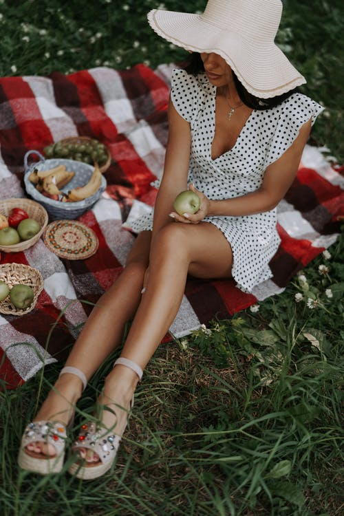 Woman having picnic with fruits on meadow