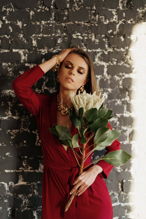Stylish woman with blooming protea near brick wall