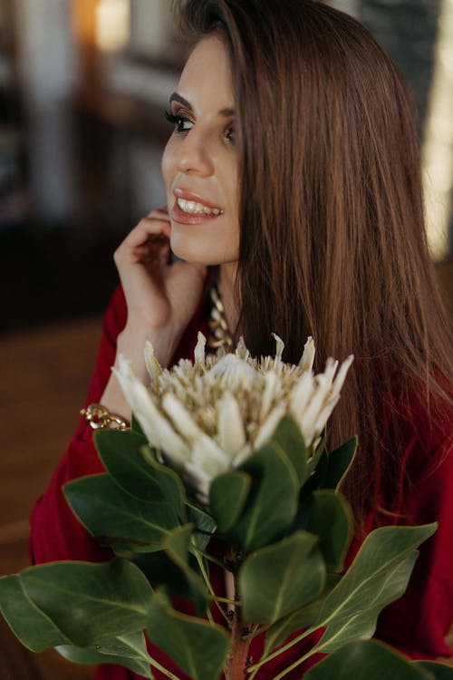 Smiling woman with blooming exotic flower