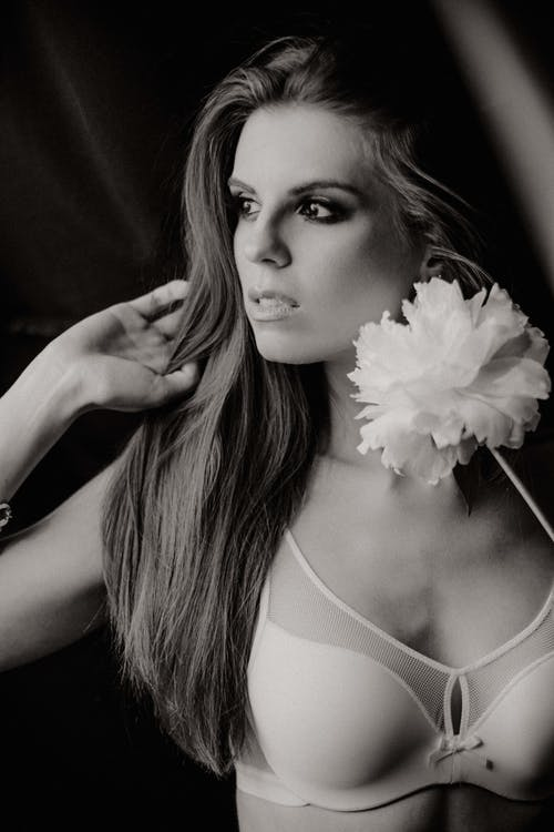 Alluring woman with blossoming flower wearing lingerie