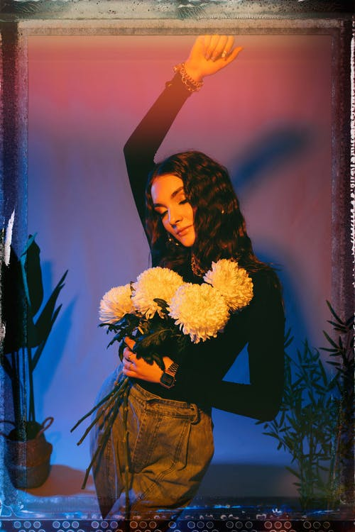 Film photo of charming young female in stylish outfit with closed eyes standing near wall with arm raised and white chrysanthemum flowers