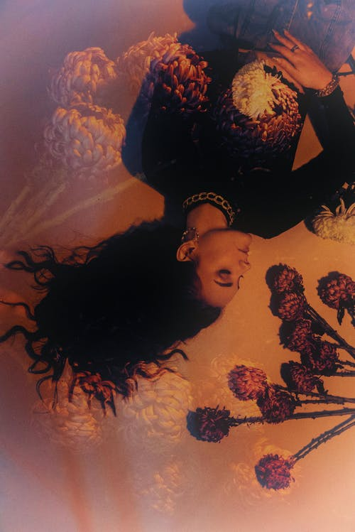Double exposure of female with eyes closed resting among blooming flowers with tender petals in ultraviolet light