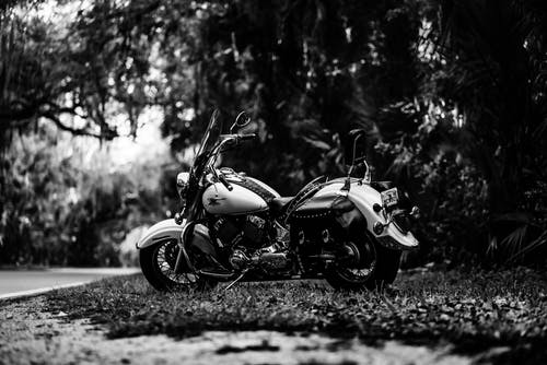 Grayscale Photo of a Motorcycle Parked Outside