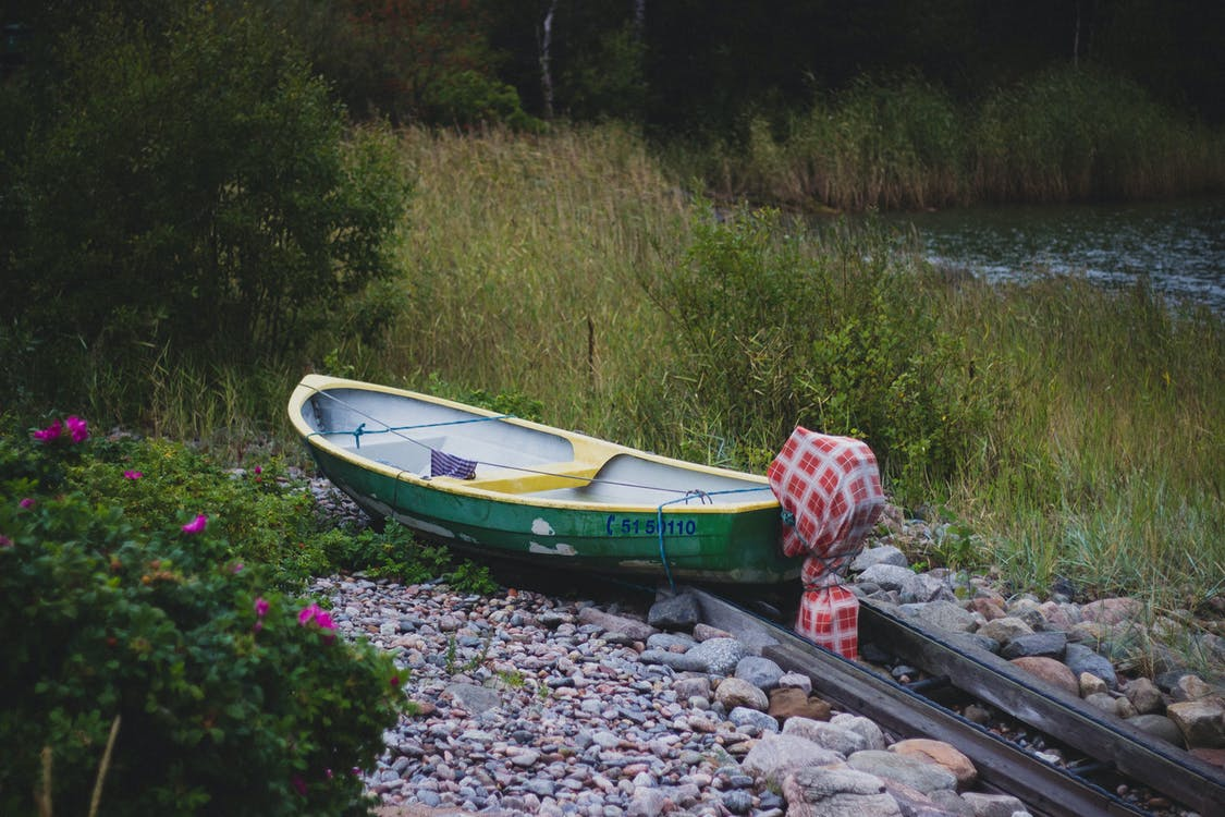 Green and Yellow Canoe Near Lake