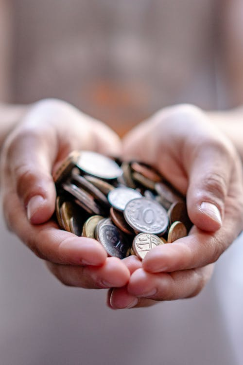 Crop anonymous person demonstrating heap of coins in hands demonstrating concept of savings