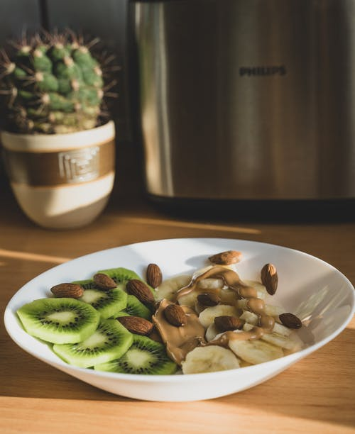 Slices of Kiwi and Banana With Nuts on White Serving Bowl