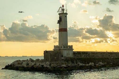 Old lighthouse on rocky breakwater against sundown sky