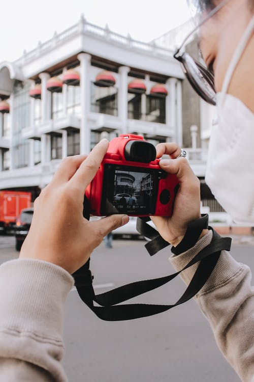 Person Holding Red and Black Digital Camera