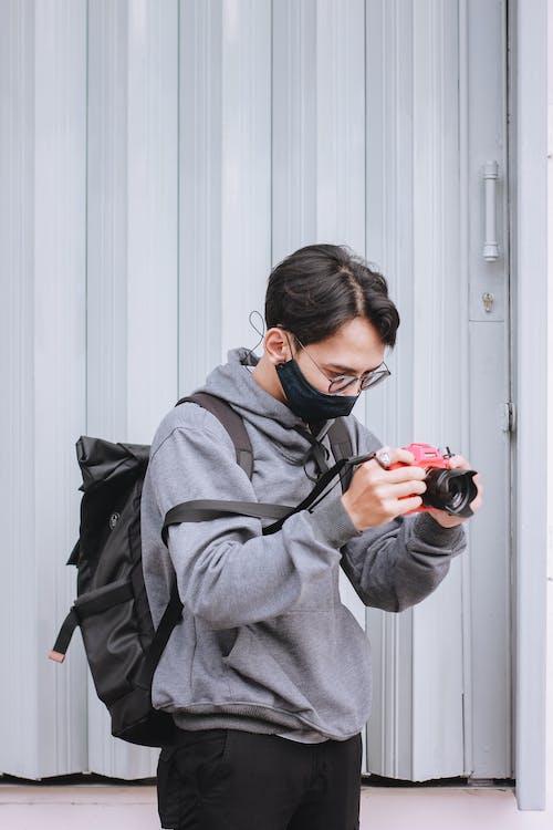Woman in Gray Coat Holding Black Dslr Camera