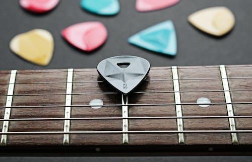 Close-Up Shot of a Guitar Pick on a Fretboard