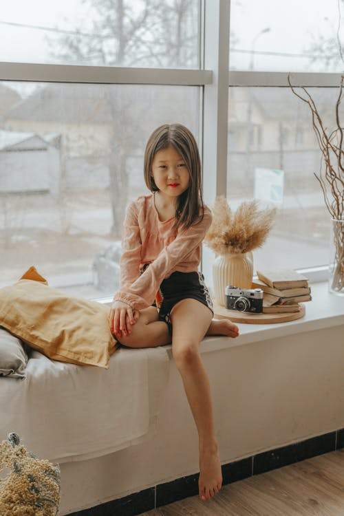 Content ethnic girl in trendy wear sitting on windowsill and looking at camera while chilling at home