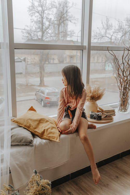 Peaceful Asian girl sitting on windowsill in cozy room and looking out of window