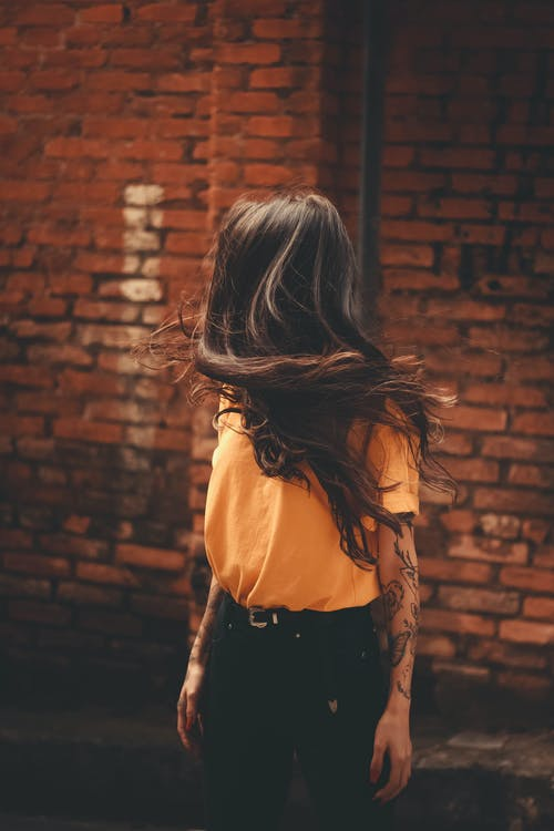 Woman in Yellow Shirt Standing Near Brick Wall