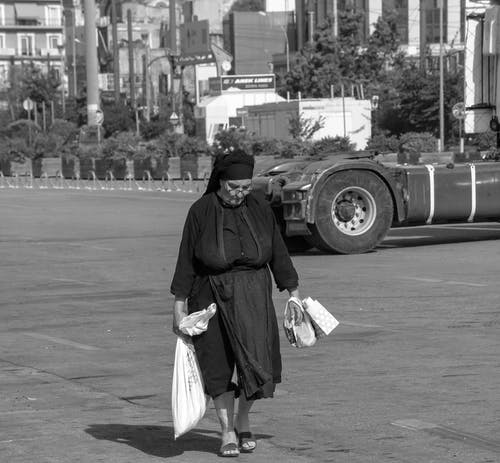 Woman in Black and White Dress Walking on Sidewalk