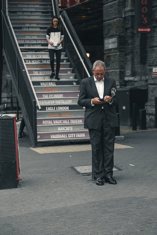 Man in Black Suit Standing Beside Red and Black Trash Bin