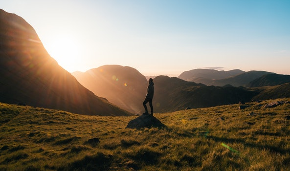 Silhouette Photography of Person Standing on Green Grass in Front of Mountains during Golden Hour
