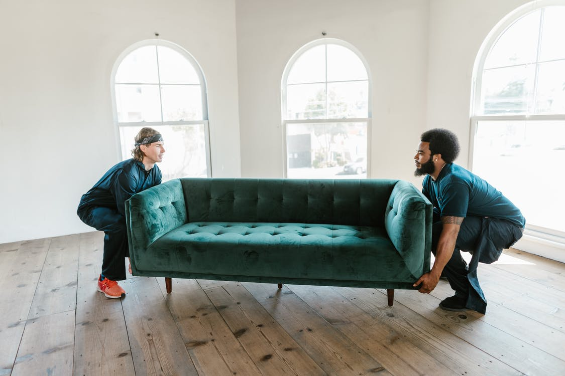 Man and Woman Sitting on Green Couch