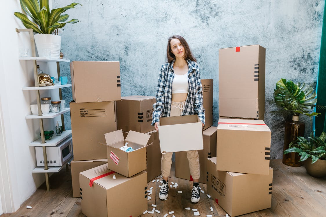 Woman in Black and White Checkered Dress Shirt Standing Beside Brown Cardboard Boxes