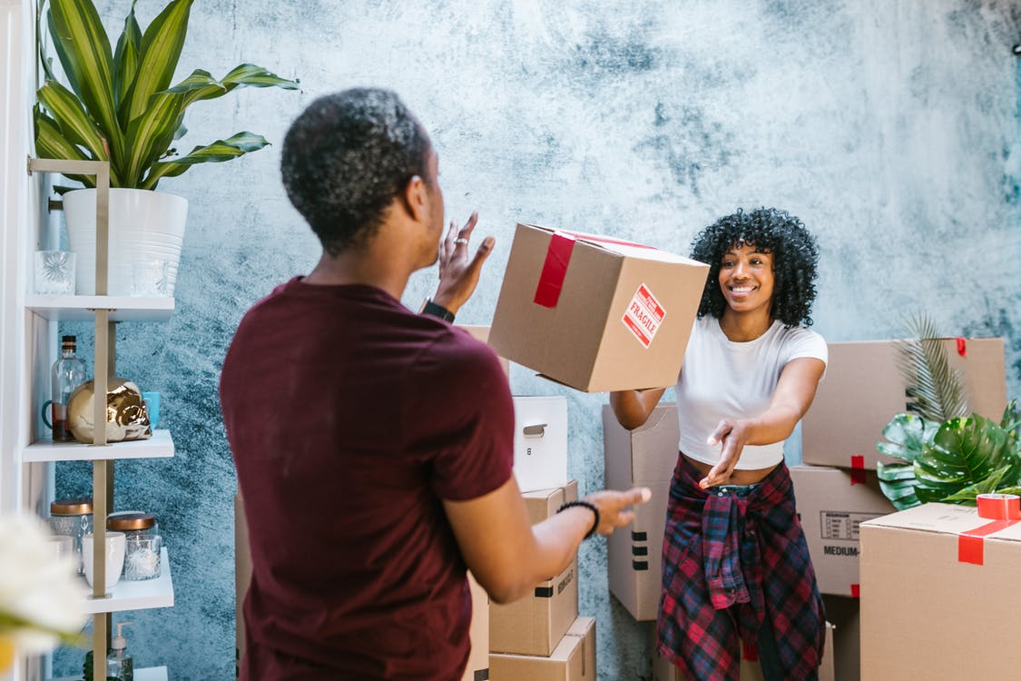 A woman handling over the box to a man while moving