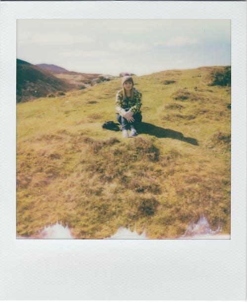 Woman in Black Jacket Sitting on Green Grass Field