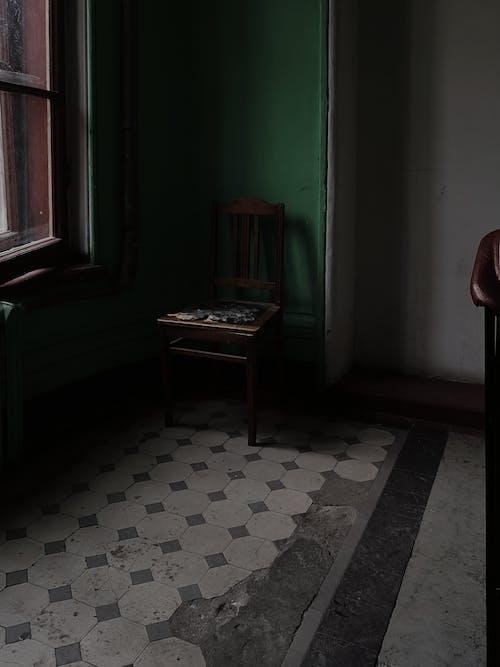 Shabby building interior with chair near window