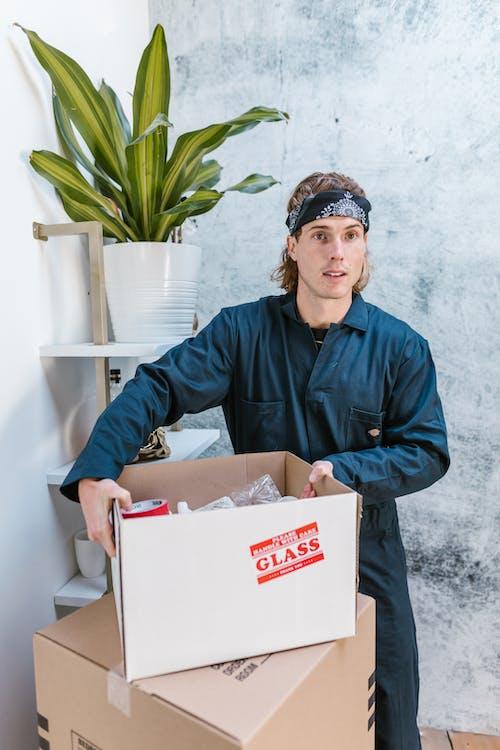 Man in Blue Dress Shirt Holding White Cardboard Box