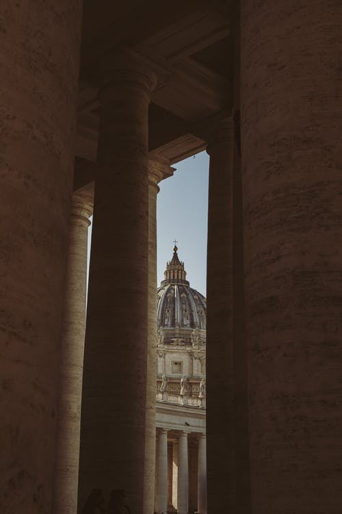 Aged stone columns in Rome against ornamental stucco roof of Saint Peters cathedral