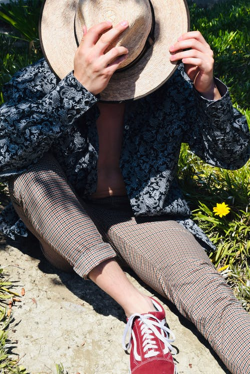 Unrecognizable trendy model in straw hat and gumshoe in sunlight