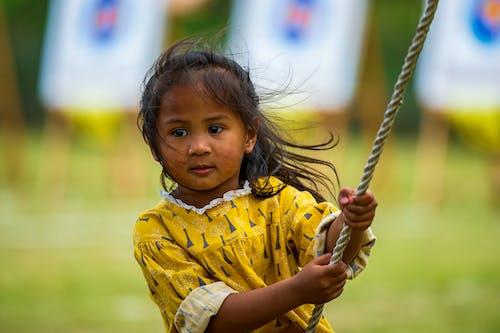 Girl Wearing Yellow Shirt Holding a Rope