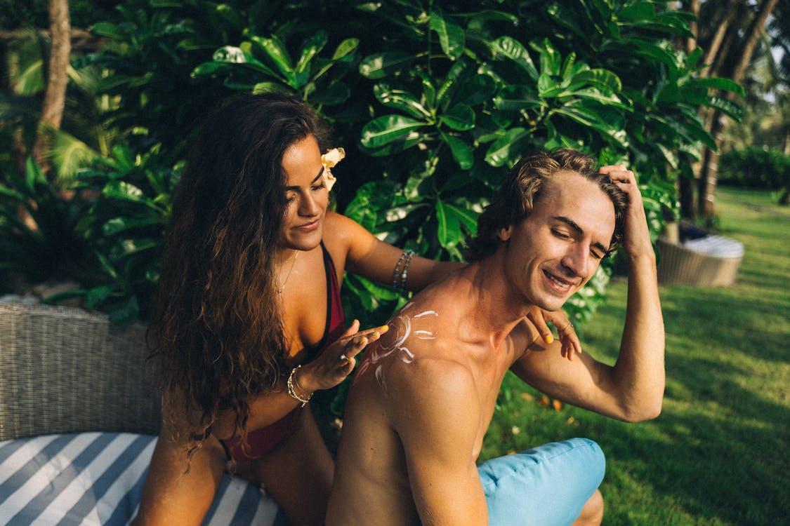 Topless Woman in Blue Denim Shorts Sitting on Green Grass