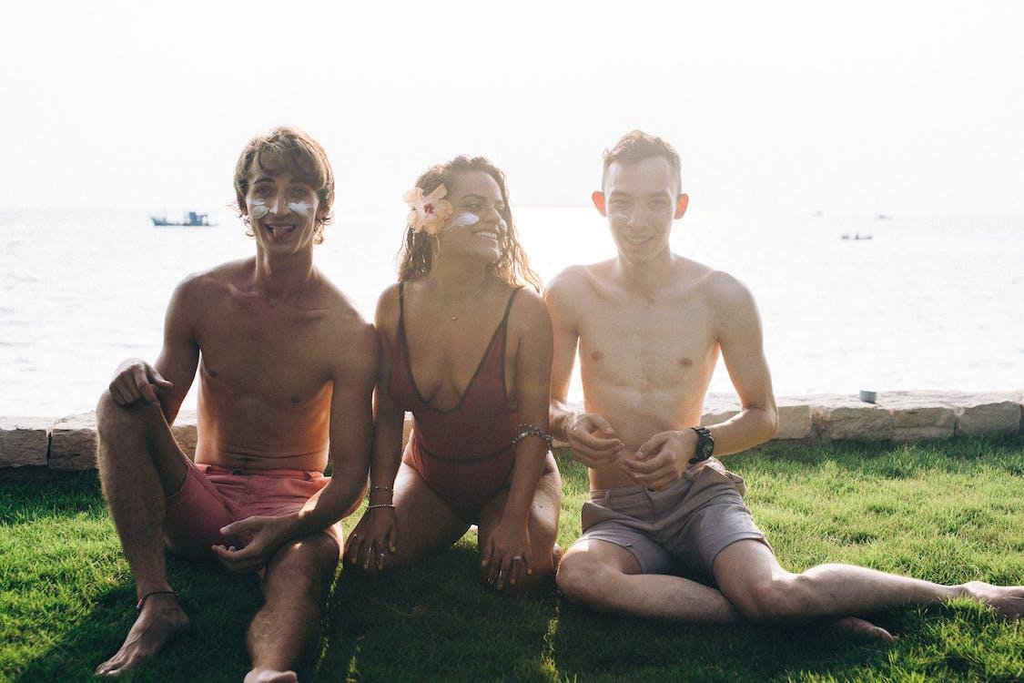 3 Topless Men Sitting on Green Grass Field