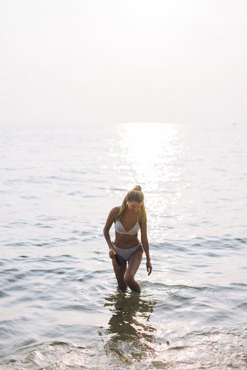 Woman in White Bikini Standing on Water