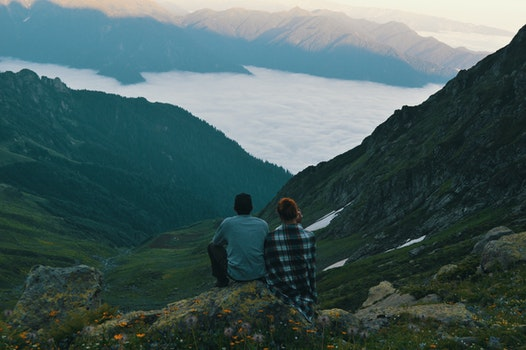 Two Person Sitting on Edge of Mountain Photograph