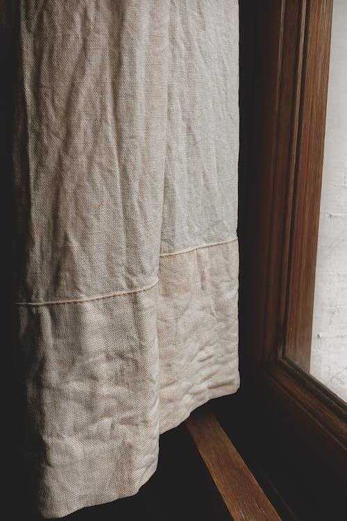White Textile Near Brown Wooden Door
