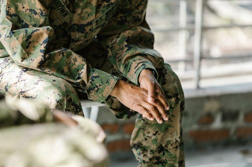 Photo of Person in Green and Brown Camouflage Uniform