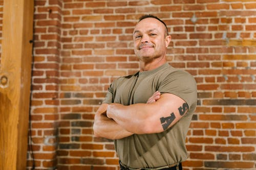 Photo of Soldier Standing in front of Brick Wall