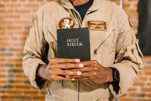 Photo of Man Holding Holy Bible