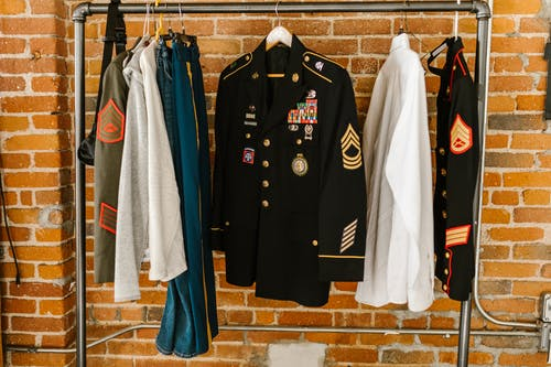 Photo of Military Uniforms Hanging on Clothing Rack
