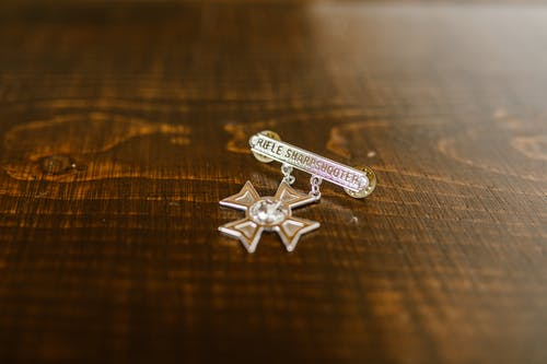 Close-Up Photo of Silver Cross Pendant on Wooden Surface