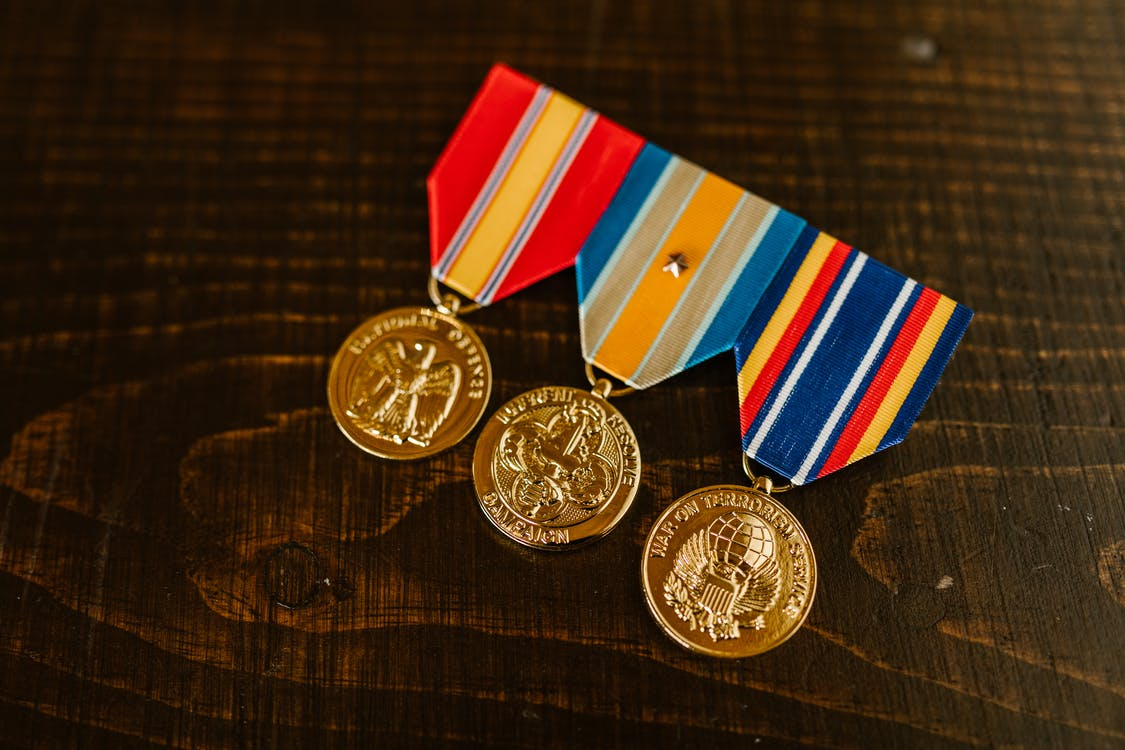Close-Up Photo of Medals on Wooden Surface
