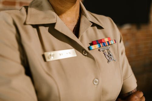 Close-Up Photo of Person Wearing Beige Military Uniform