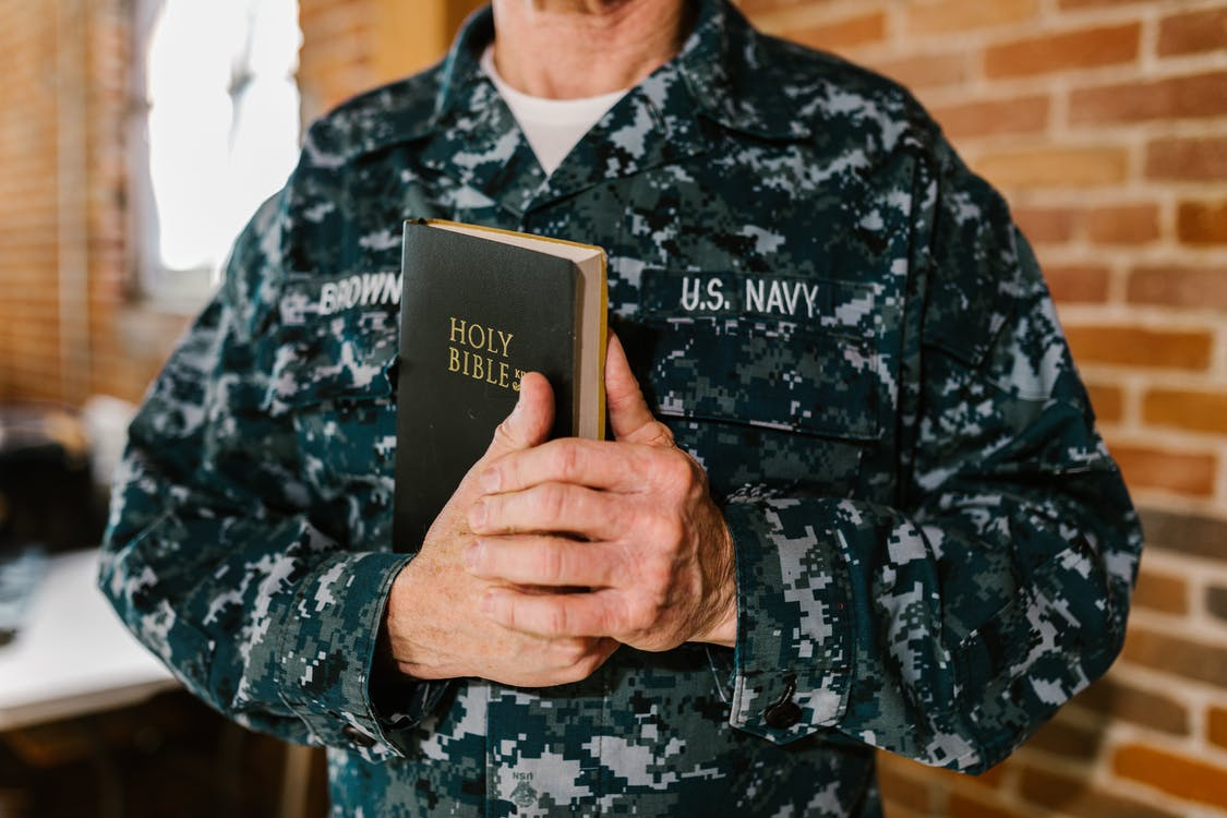 Photo of Man in Military Uniform Holding Holy Bible