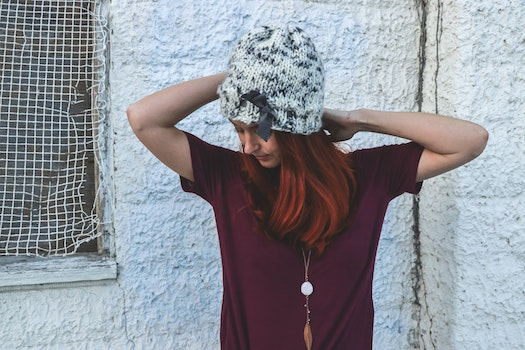 Woman in White and Black Knit Cap Posing Near White Wall